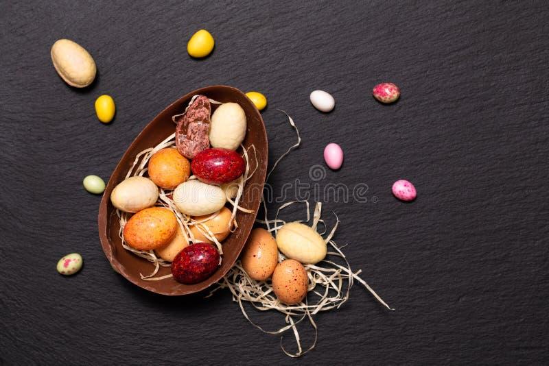 Uova di Pasqua variopinte della caramella e del cioccolato di concetto dell'alimento di festa sul piatto nero dell'ardesia con lo immagine stock