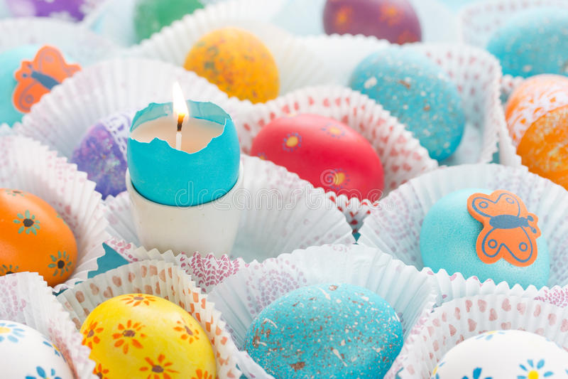 Uova di Pasqua variopinte e candela bruciante immagine stock