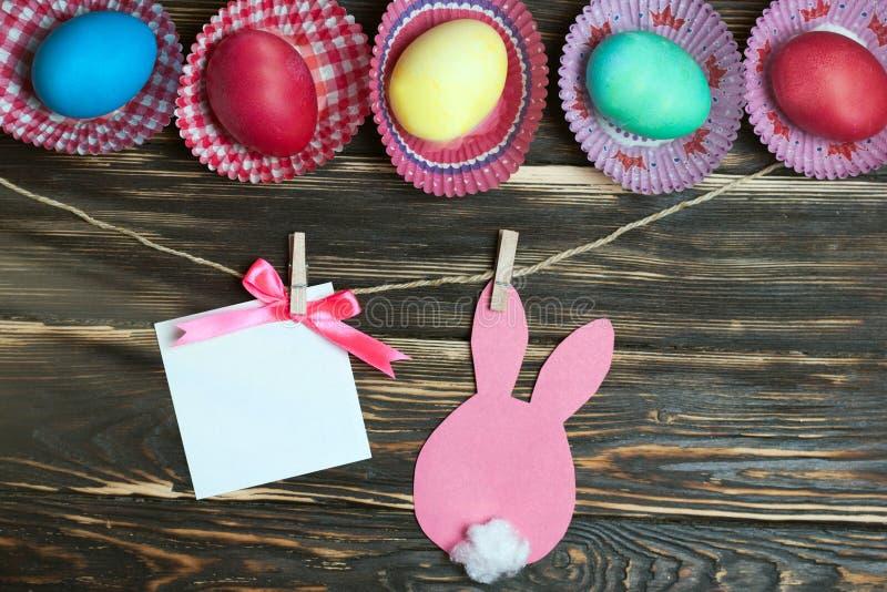 Uova di Pasqua variopinte e conigli di carta Cartolina d'auguri su fondo di legno Mercanzie di Pasqua in azione immagini stock