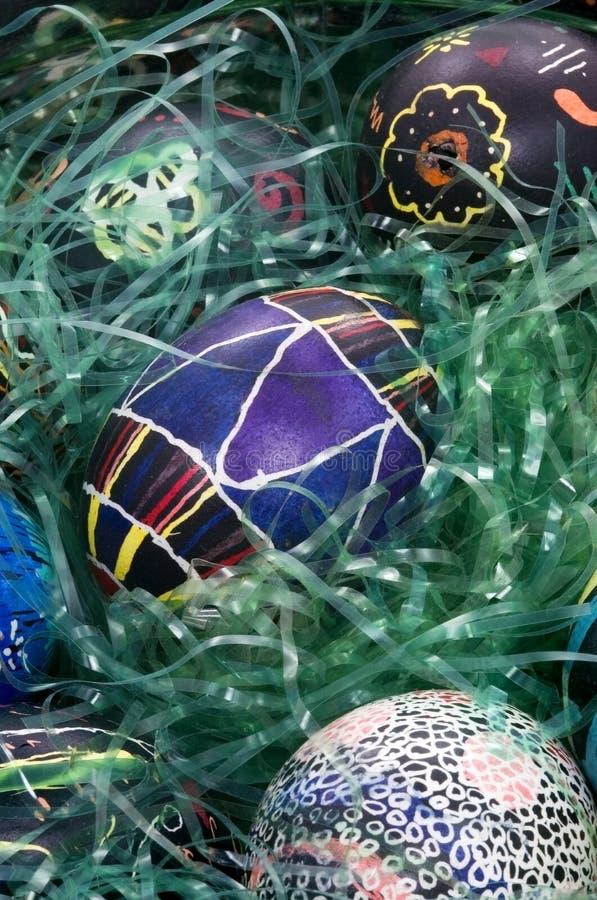 Uova di Pasqua Variopinte in erba - disegno di Geometic nella metà immagini stock