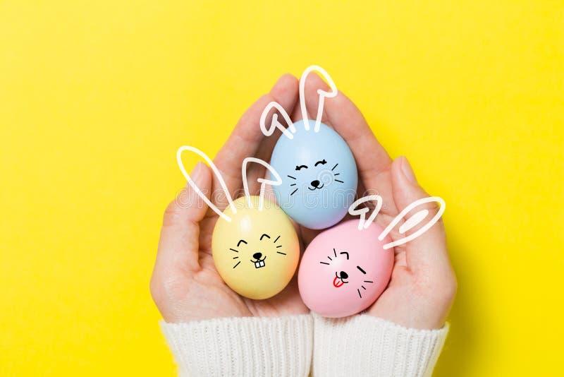 Uova di Pasqua variopinte su fondo giallo immagini stock