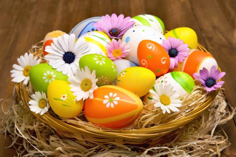 Uova di Pasqua Variopinte in un cestino immagini stock