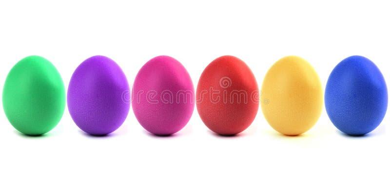 Uova di Pasqua variopinte in una fila immagini stock