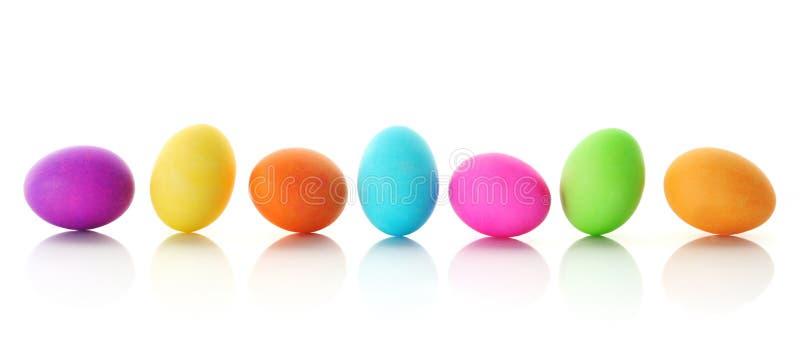 Uova di Pasqua Variopinte in una riga immagini stock