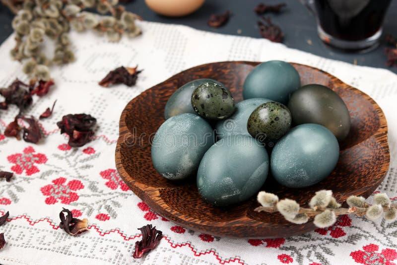 Uova di quaglia e del pollo su un piatto, dipinto con tè dai petali di una rosa o di un ibisco sudanese fotografia stock libera da diritti