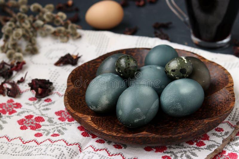 Uova di quaglia e del pollo su un piatto, dipinto con tè dai petali di una rosa o di un ibisco sudanese immagine stock
