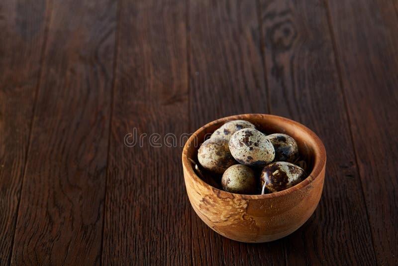 Uova di quaglia fresche in una ciotola di legno su un fondo di legno scuro, vista superiore, primo piano fotografia stock