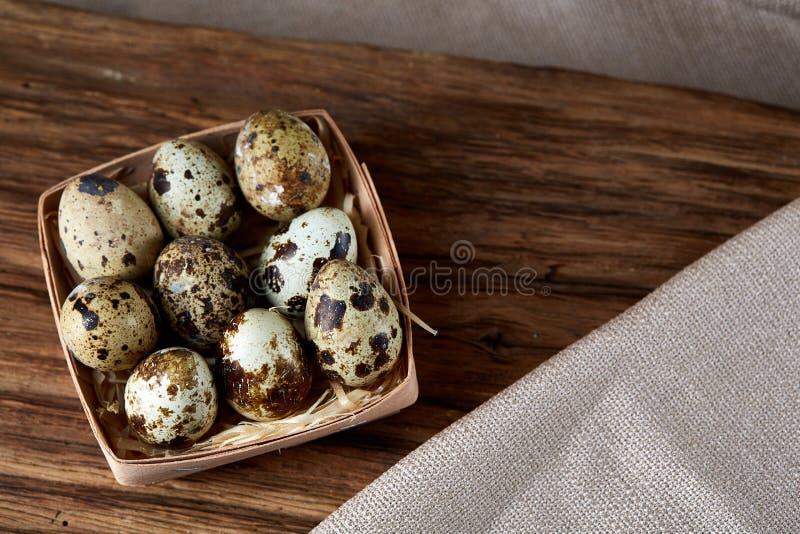 Uova di quaglia nel contenitore sul pezzo di legno sopra la tovaglia homespun, primo piano, vista dell'angolo alto, fuoco seletti immagine stock libera da diritti