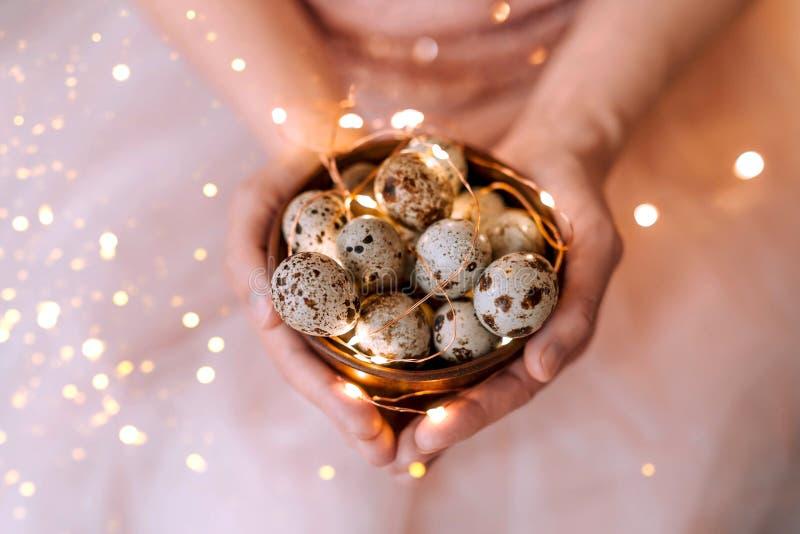 Uova di quaglia in un piatto di legno nelle mani di una ragazza su un fondo rosa immagine stock