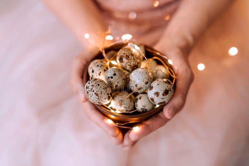 Uova di quaglia in un piatto di legno nelle mani di una ragazza su un fondo rosa fotografie stock libere da diritti