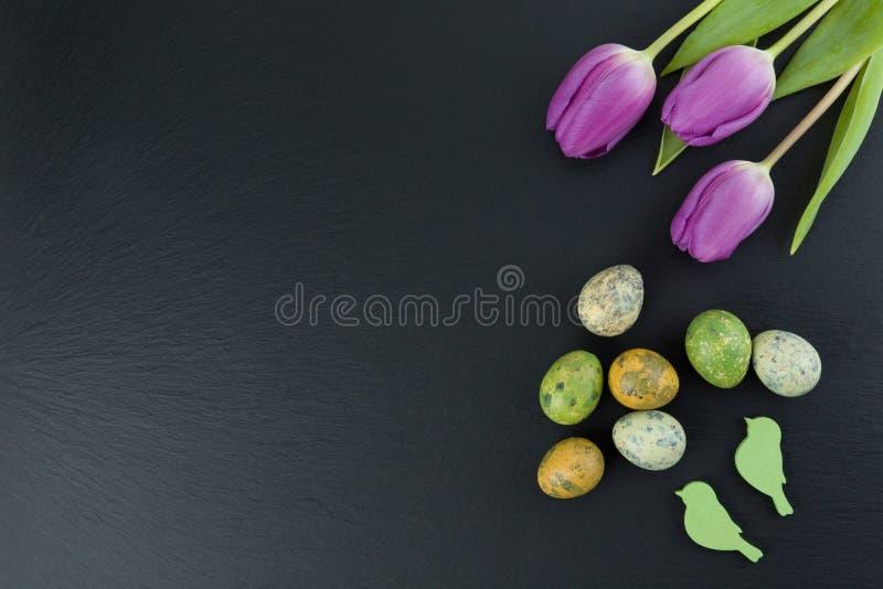 Uova di quaglia variopinte e fiori del tulipano ed uccelli di legno verdi sulla tavola di pietra Vista superiore con lo spazio de fotografie stock
