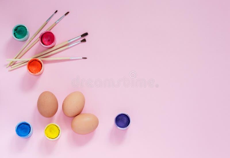 Uova di verniciatura del pollo per la celebrazione di Pasqua Uova decorate, pitture variopinte e spazzole sul rosa con copyspace immagine stock libera da diritti