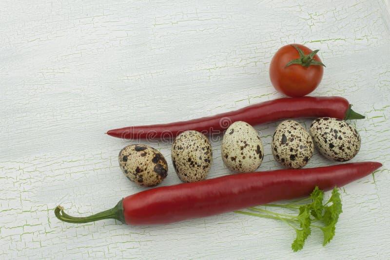 Uova e verdure di quaglia al vecchio vassoio di legno ombreggiato incrinato fotografie stock