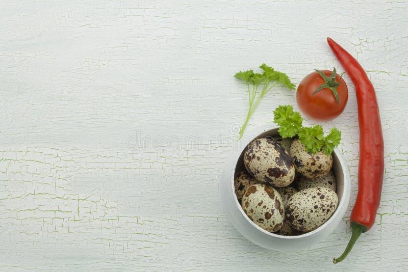 Uova e verdure di quaglia al vecchio vassoio di legno ombreggiato incrinato immagine stock