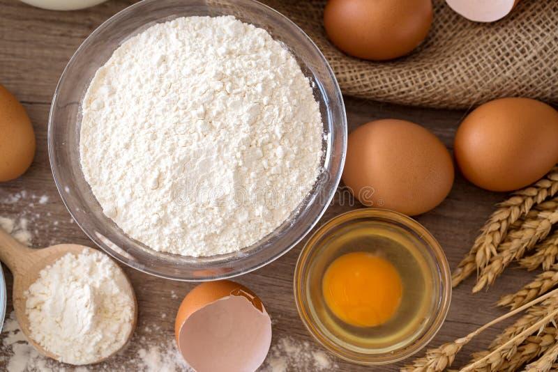 Uova ed ingredienti di base della farina per cuocere vista superiore fotografia stock