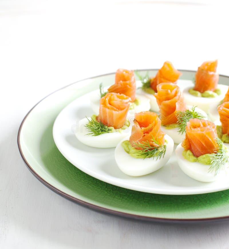 Uova farcite con il materiale da otturazione ed il salmone affumicato dell'avocado fotografie stock libere da diritti