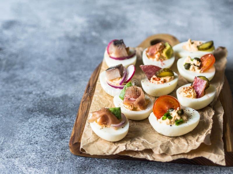 Uova farcite con varia guarnizione Prosciutto di Parma, aringa, cetriolo marinato, salsiccia, ravanello, pomodoro, capperi e sesa immagine stock
