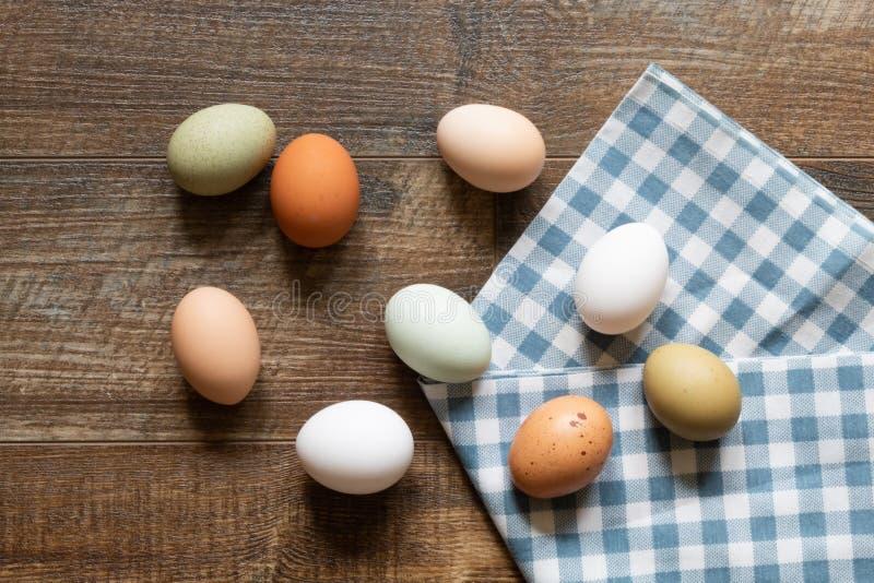Uova fresche con l'asciugamano blu e bianco del percalle su fondo di legno immagini stock