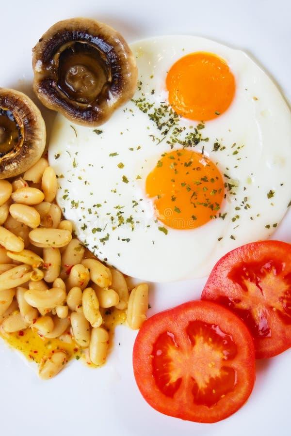 Uova fritte con i funghi, i fagioli ed il pomodoro immagini stock