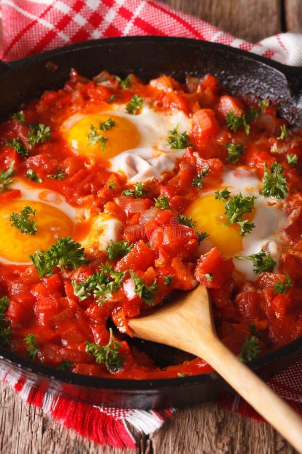 Uova fritte di Shakshuka con la fine della salsa su in una padella Vertic fotografia stock