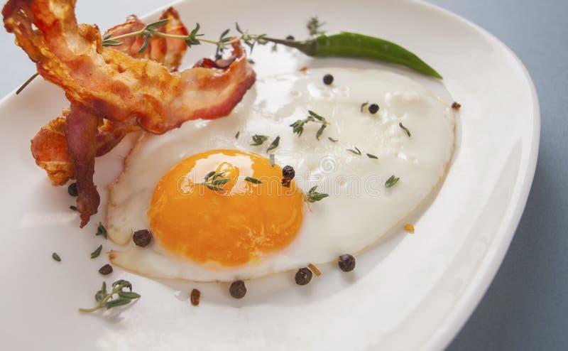 Uova fritte e bacon della prima colazione vicini su su un piatto ovale immagini stock libere da diritti
