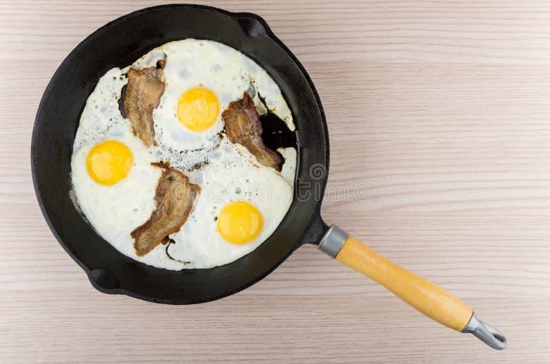 Uova fritte e bacon in padella del ghisa sulla tavola immagini stock libere da diritti