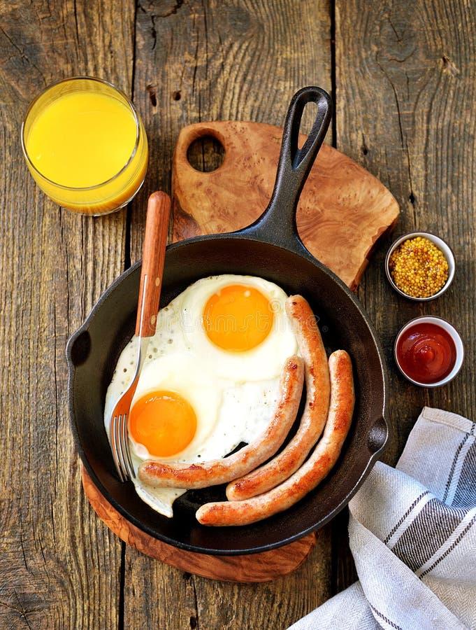 Uova fritte e salsiccie sottili in una padella del ghisa Vista superiore della prima colazione Copi lo spazio fotografie stock
