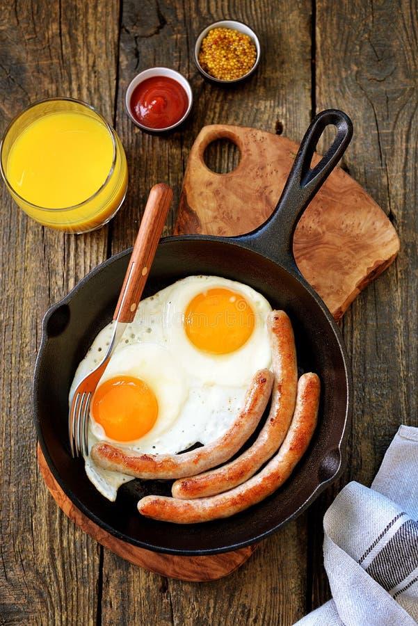 Uova fritte e salsiccie sottili in una padella del ghisa Vista superiore della prima colazione Copi lo spazio fotografia stock libera da diritti