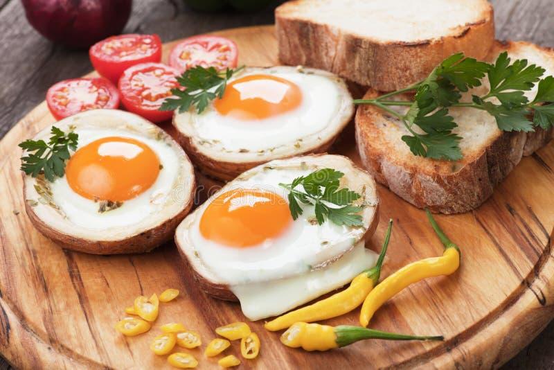 Uova fritte nelle coperture della patata fotografia stock