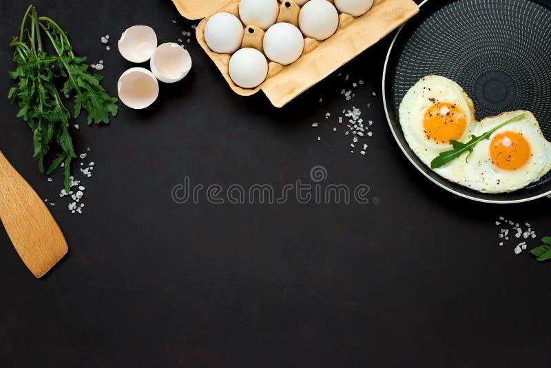 Uova fritte in padella con le foglie, il sale ed il pepe della rucola per la prima colazione su fondo di legno nero Vista superio immagini stock libere da diritti