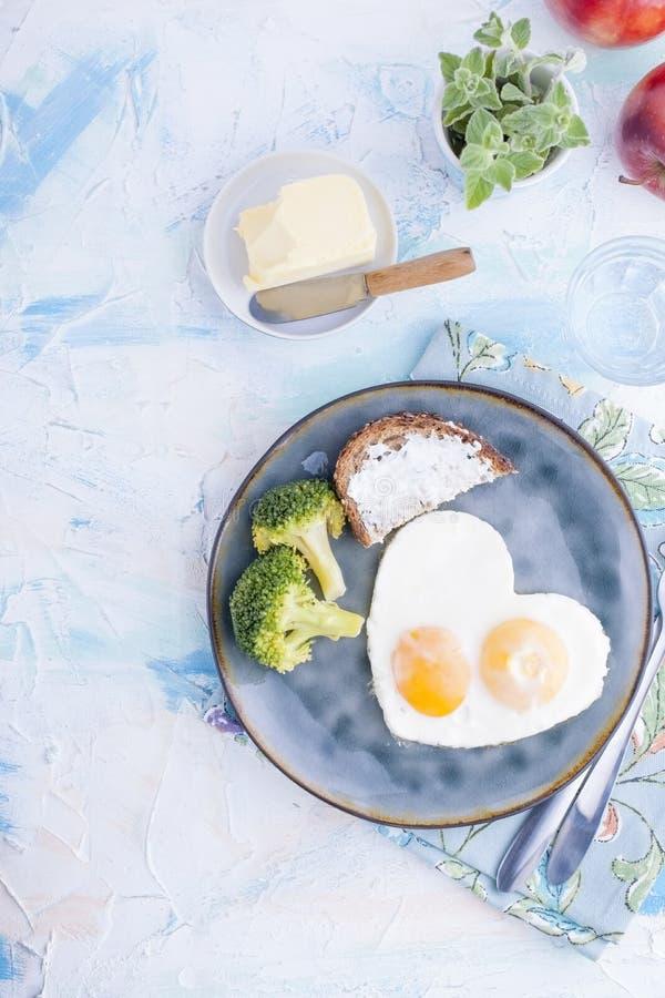 Uova fritte sotto forma di cuore Su un piatto scuro con i broccoli e la tazza blu del pane tostato con tè, mele, burro per la pri fotografia stock