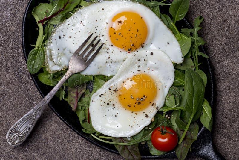 Uova fritte sulla pentola con le erbe ed i pomodori ciliegia con la forcella a fondo marrone immagine stock