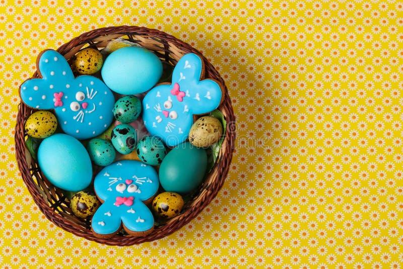 Uova gialle e blu dei conigli dei pan di zenzero di Pasqua, del pollo e di quaglia in un canestro di vimini, vista superiore immagine stock libera da diritti