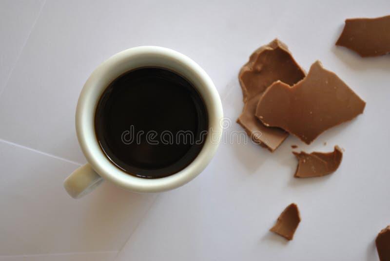 Uova incrinate cioccolato e tazza di caffè espresso Backgr bianco immagini stock libere da diritti