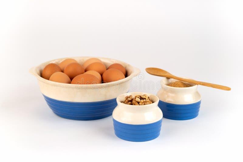 Uova libere organiche fresche della gamma dell'azienda agricola, noci, zucchero organico in ciotole blu e bianche immagini stock libere da diritti