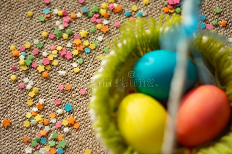 Uova multicolori nel canestro festivo di pasqua sul tovagliolo della tela immagini stock