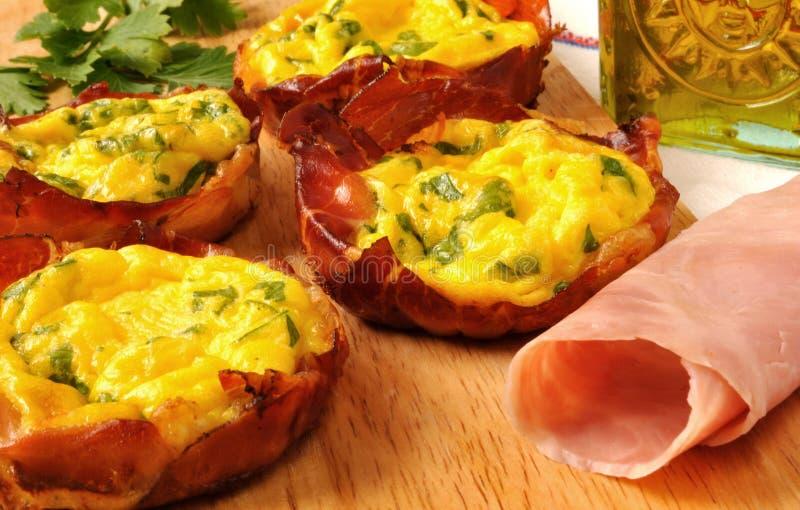 Uova nei cestini della pancetta affumicata immagini stock libere da diritti