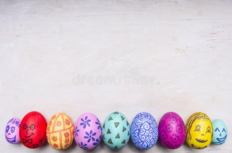 Uova ornamentali colorate per Pasqua con il confine dipinto dei fronti, posto per la fine rustica di legno di vista superiore del fotografie stock
