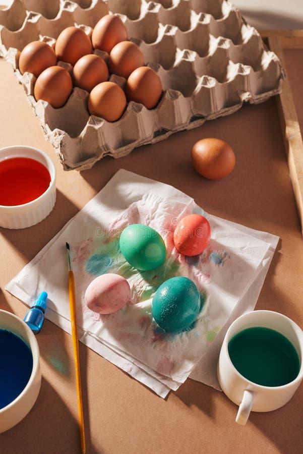 Uova, pitture variopinte, spazzole, matite su un fondo di legno, uova di coloritura, preparanti per Pasqua, festa stagionale dell immagini stock