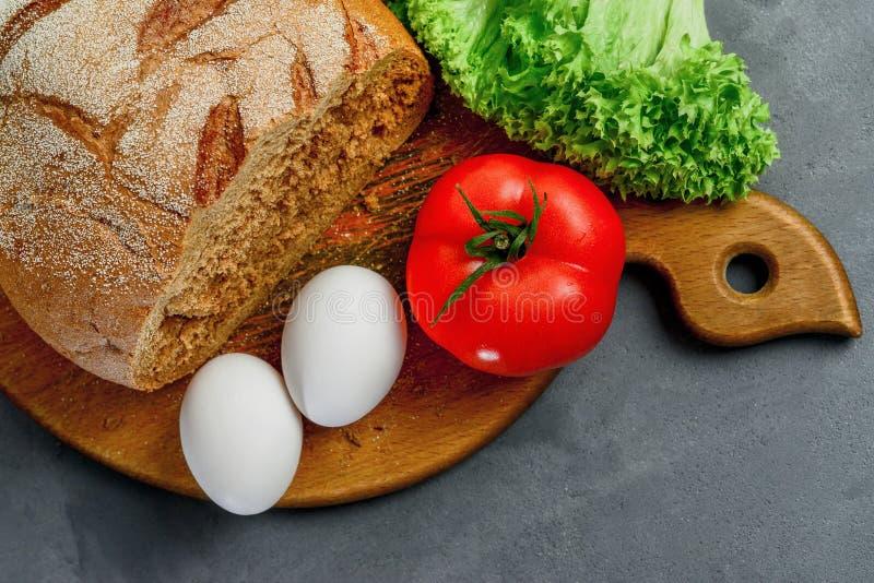 Uova, pomodoro, foglie della lattuga, pane Bordo di legno con gli ingredienti per cucinare Da sopra fotografie stock libere da diritti