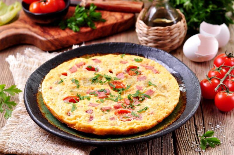 Uova rimescolate con il prosciutto, il pomodoro ed il prezzemolo fotografia stock