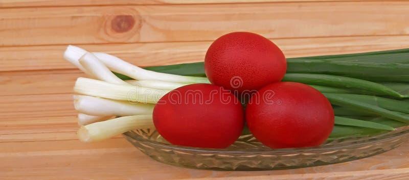 Uova rosse di Pasqua e delle cipolle di inverno su fondo di legno fotografia stock