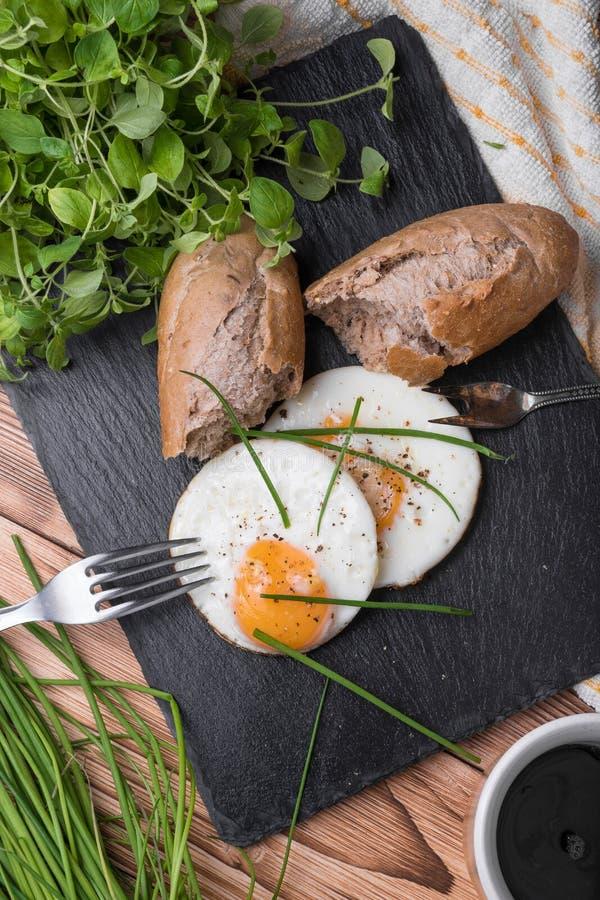 Uova rotonde di Roeasted con pane fresco sul bordo di pietra nero fotografie stock libere da diritti