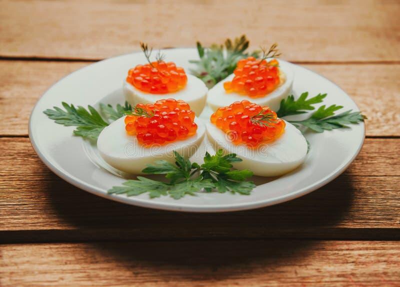Uova sode mezzi con il caviale del salmone rosso immagini stock
