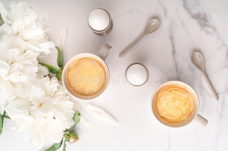 Uova sode in portauova ceramici e due tazze di caffè su fondo di bella peonia bianca Concetto della prima colazione Vista superio fotografia stock