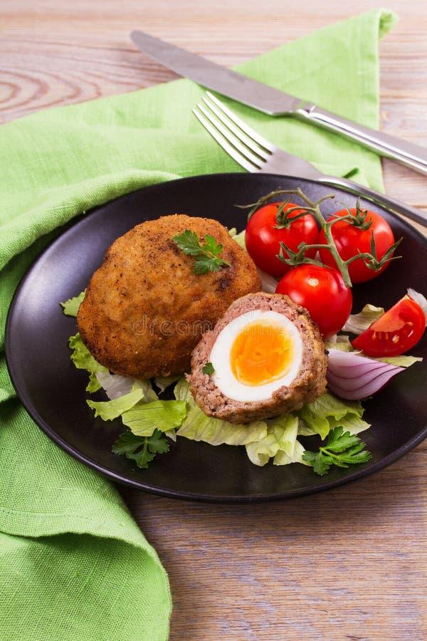 Uova sodo/carne per salsiccia su un piatto con i pomodori ciliegia e l'insalata immagine stock
