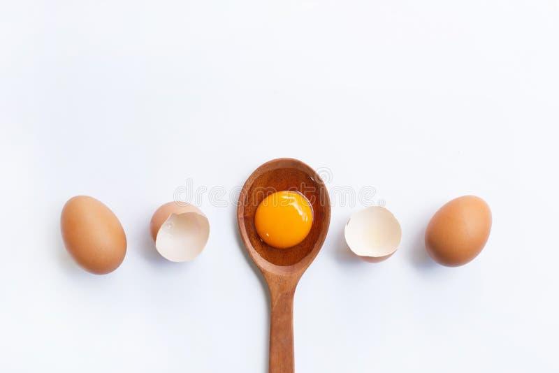 Uova, tuorlo d'uovo sul cucchiaio di legno isolato fotografie stock