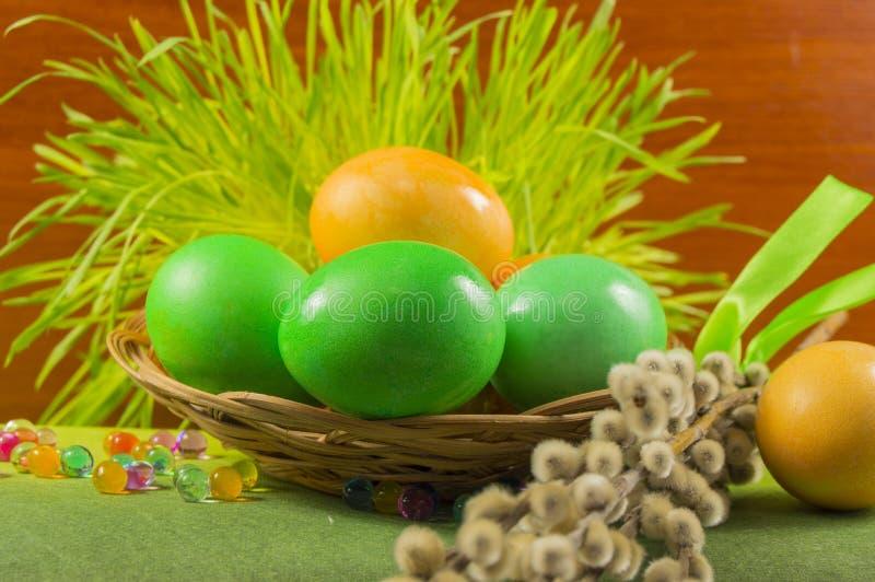 Uova in un canestro di vimini con i ramoscelli del salice, fuoco selettivo immagine stock