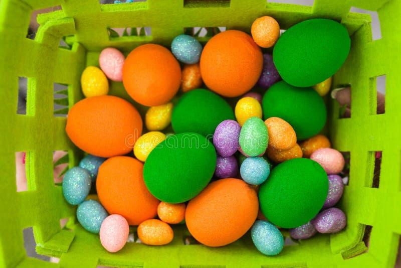 Uova variopinte di Pasqua delle dimensioni differenti in un canestro fotografia stock