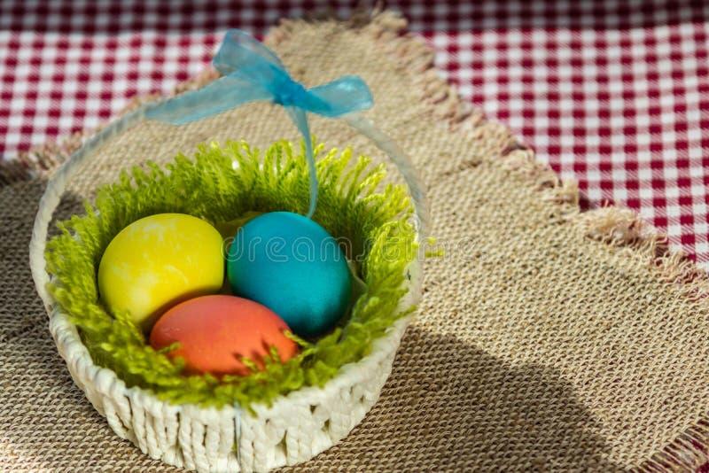 Uova variopinte di Pasqua in un canestro bianco fotografia stock libera da diritti
